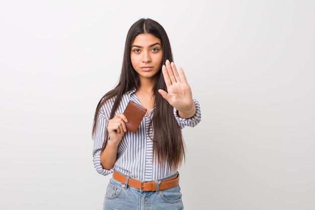 Jovem mulher árabe segurando uma carteira em pé com a mão estendida, mostrando o sinal de stop, impedindo-o.
