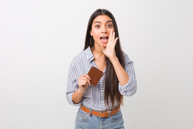 Jovem mulher árabe segurando uma carteira gritando animado para a frente.
