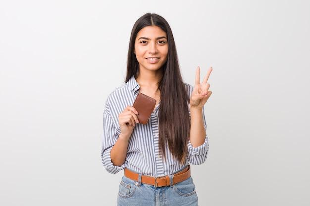 Jovem mulher árabe segurando uma carteira mostrando o número dois com os dedos