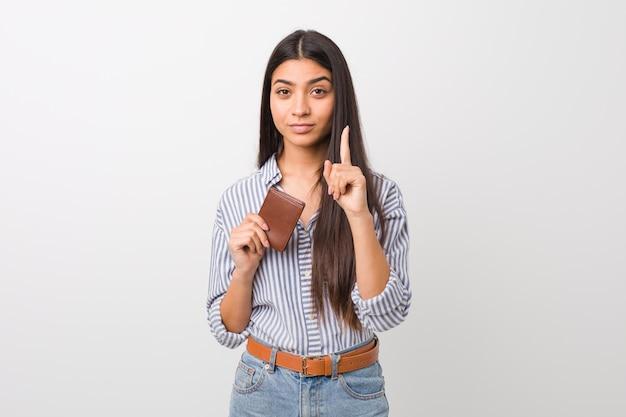 Jovem mulher árabe segurando uma carteira, mostrando o número um com o dedo.