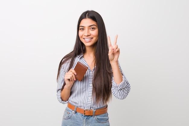 Jovem mulher árabe segurando uma carteira mostrando sinal de vitória e sorrindo amplamente.