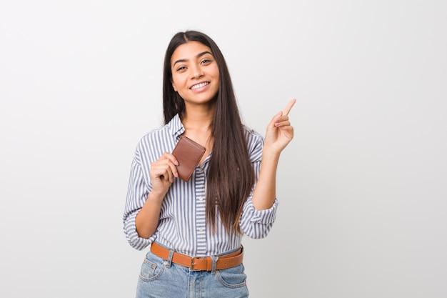 Jovem mulher árabe segurando uma carteira sorrindo alegremente apontando com o dedo indicador fora.