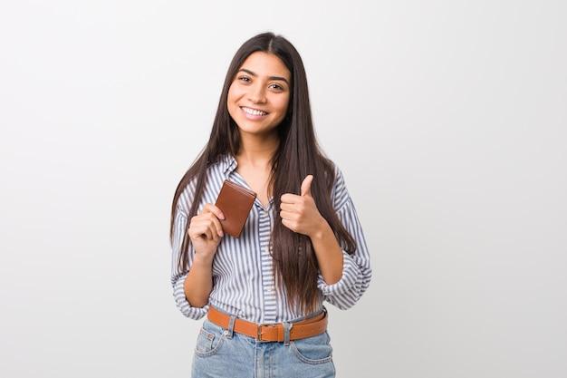 Jovem mulher árabe segurando uma carteira sorrindo e levantando o polegar