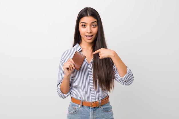 Jovem mulher árabe segurando uma carteira surpreendeu apontando para si mesmo, sorrindo amplamente.