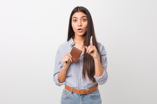 Jovem mulher árabe segurando uma carteira, tendo uma ótima idéia, conceito de criatividade.