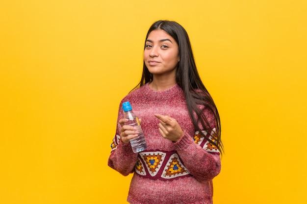 Jovem mulher árabe segurando uma garrafa de água, apontando com o dedo para você, como se estivesse convidando para se aproximar.