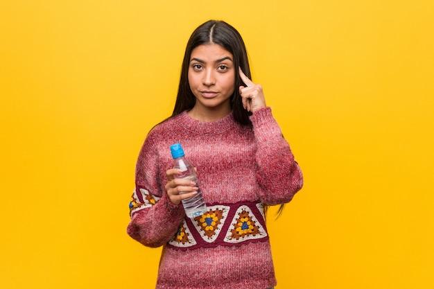 Jovem mulher árabe segurando uma garrafa de água, apontando seu templo com o dedo, pensando, focado em uma tarefa.