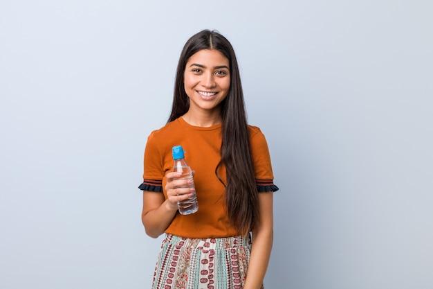 Jovem mulher árabe segurando uma garrafa de água feliz, sorridente e alegre.