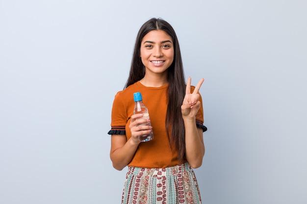 Jovem mulher árabe segurando uma garrafa de água, mostrando o número dois com os dedos.