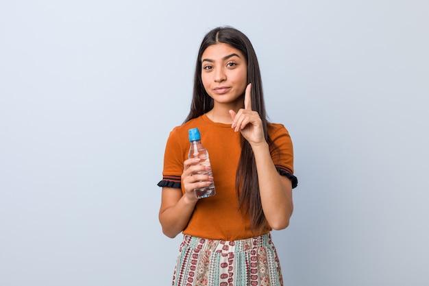 Jovem mulher árabe segurando uma garrafa de água, mostrando o número um com o dedo.