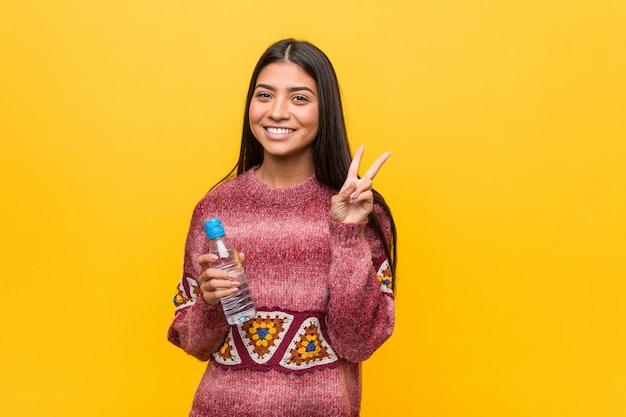 Jovem mulher árabe segurando uma garrafa de água, mostrando sinal de vitória e sorrindo amplamente