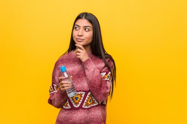 Jovem mulher árabe segurando uma garrafa de água, olhando de soslaio com expressão duvidosa e cética.