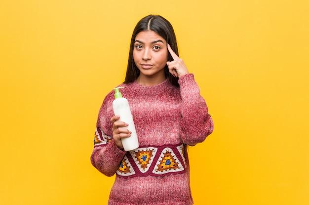 Jovem mulher árabe segurando uma garrafa de creme apontando seu templo com o dedo, pensando, focado em uma tarefa.