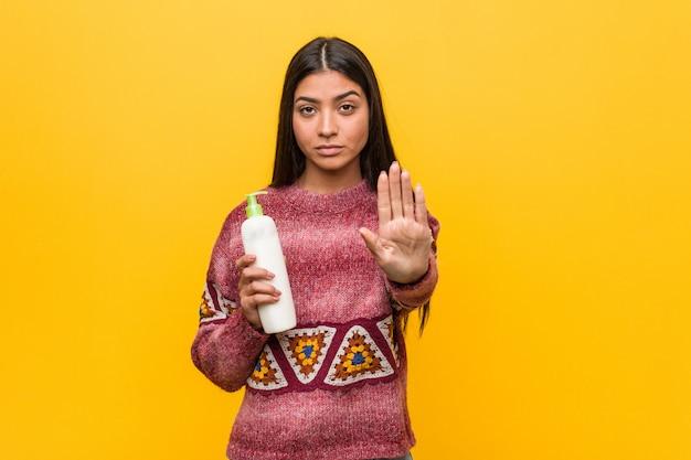 Jovem mulher árabe segurando uma garrafa de creme em pé com a mão estendida, mostrando o sinal de stop, impedindo-o.