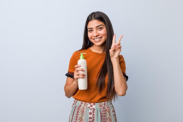 Jovem mulher árabe segurando uma garrafa de creme mostrando sinal de vitória e sorrindo amplamente.