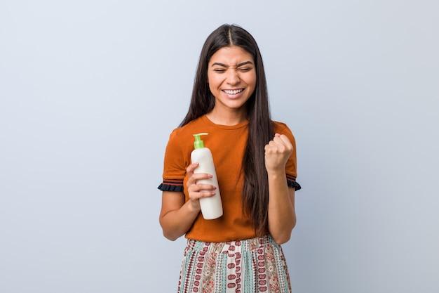 Jovem mulher árabe segurando uma garrafa de creme torcendo despreocupado e animado. conceito de vitória