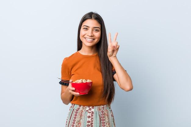 Jovem mulher árabe segurando uma tigela de cereais mostrando sinal de vitória e sorrindo amplamente.