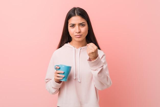 Jovem mulher árabe segurando uma xícara, mostrando o punho para a câmera, expressão facial agressiva.