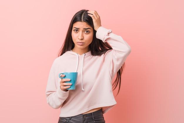 Jovem mulher árabe segurando uma xícara sendo chocada, ela se lembrou de uma reunião importante.