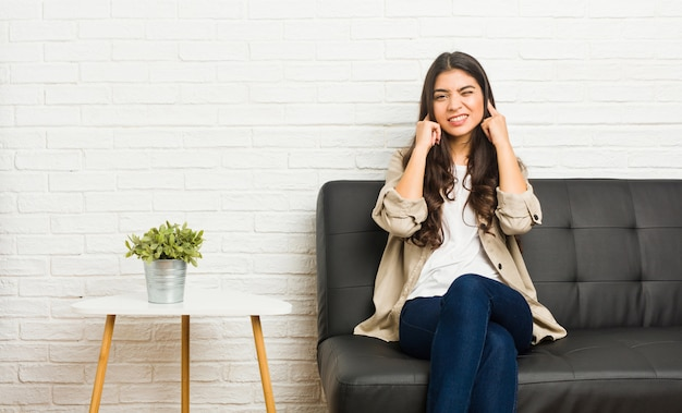 Jovem mulher árabe sentada no sofá cobrindo os ouvidos com as mãos.