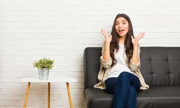 Jovem mulher árabe sentada no sofá comemorando uma vitória ou sucesso, ele fica surpreso e chocado.