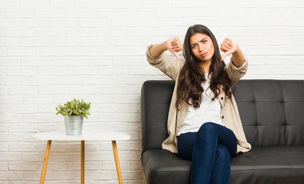 Jovem mulher árabe sentada no sofá, mostrando o polegar para baixo e expressando antipatia.
