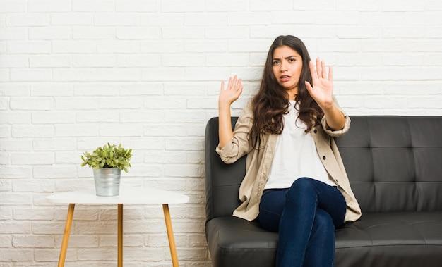 Jovem mulher árabe sentada no sofá sendo chocada devido a um perigo iminente