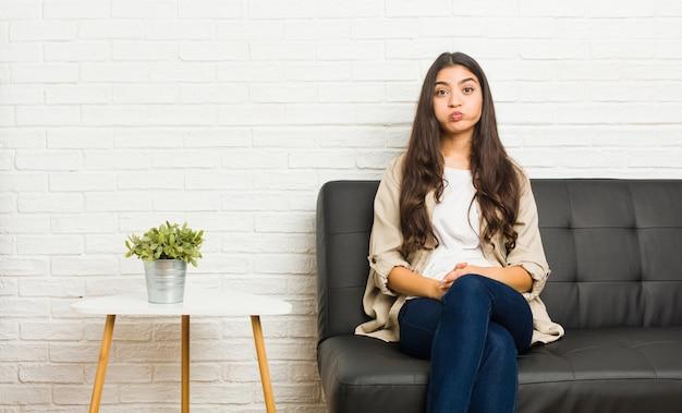Jovem mulher árabe sentada no sofá sopra as bochechas, tem expressão cansada. expressão facial.
