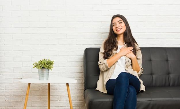 Jovem mulher árabe sentada no sofá tem expressão amigável, pressionando a palma da mão no peito. conceito de amor