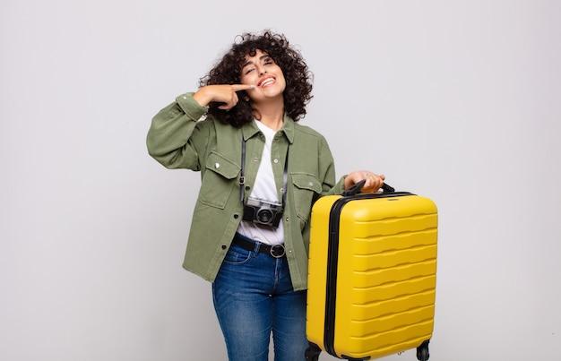 Jovem mulher árabe sorrindo com confiança apontando para o próprio conceito de viagem com um sorriso largo