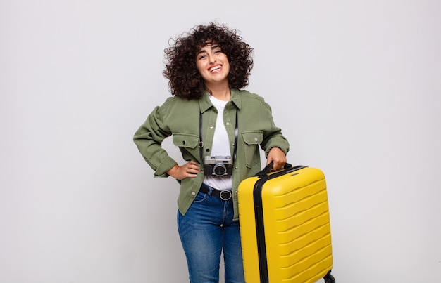 Jovem mulher árabe sorrindo feliz com uma mão no quadril e conceito de viagem com atitude confiante, positiva, orgulhosa e amigável