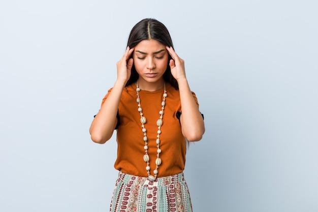 Jovem mulher árabe tocando os templos e tendo dor de cabeça.
