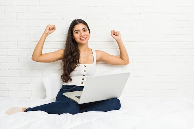Jovem mulher árabe trabalhando com seu laptop na cama mostrando força gesto com os braços