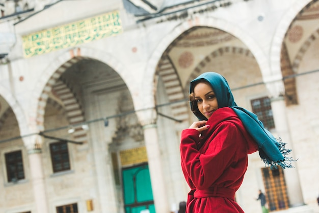 Jovem mulher árabe vestindo véu na frente de uma mesquita