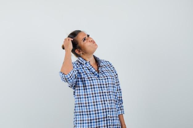 Jovem mulher arrancando a cabeça enquanto olha para cima com uma camisa quadriculada e parece perplexa.