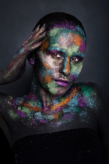 Jovem mulher artística em tinta preta e pó colorido. maquiagem escura brilhante. arte corporal criativa sobre o tema do espaço e das estrelas. projeto de pintura corporal: arte, beleza, moda.