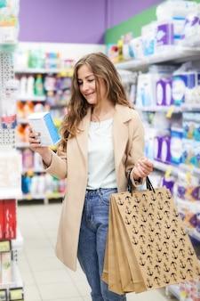 Jovem mulher às compras no supermercado e lendo informações em uma caixa. compras econômicas e úteis.