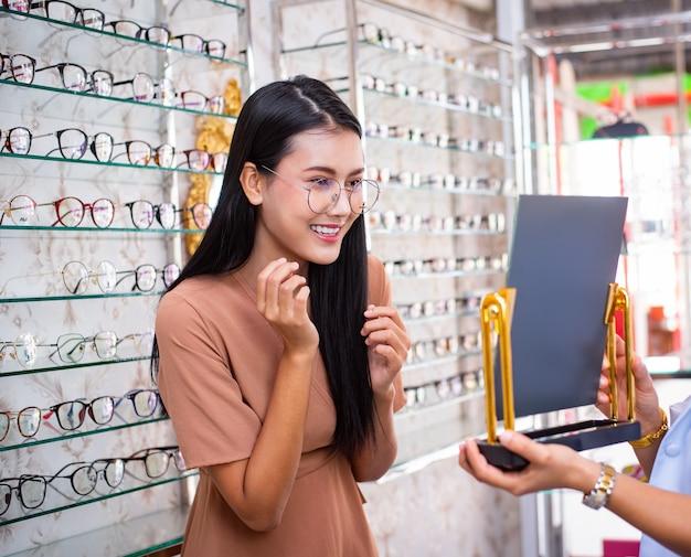 Jovem mulher ásia está escolhendo um óculos na loja de óptica.