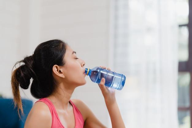 Jovem, mulher asian, água potável, porque, sentir, esgotado, descanso, após, exercício, em, sala de estar