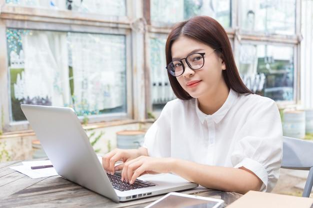 Jovem, mulher asian, com, óculos, trabalhar, ligado, dela, computador, ao ar livre, em, dela, jardim