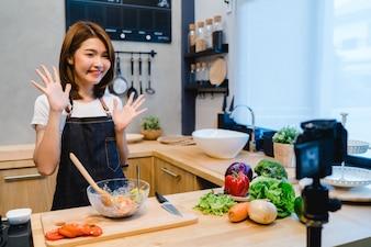 Jovem, mulher asian, em, cozinha, vídeo gravação, ligado, câmera