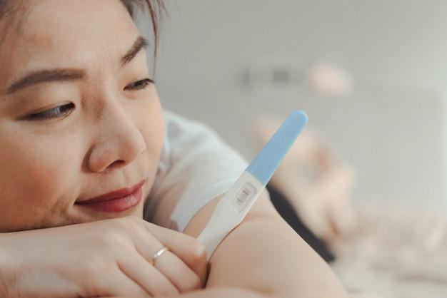 Jovem, mulher asian, olhar, teste gravidez, em, felicidade