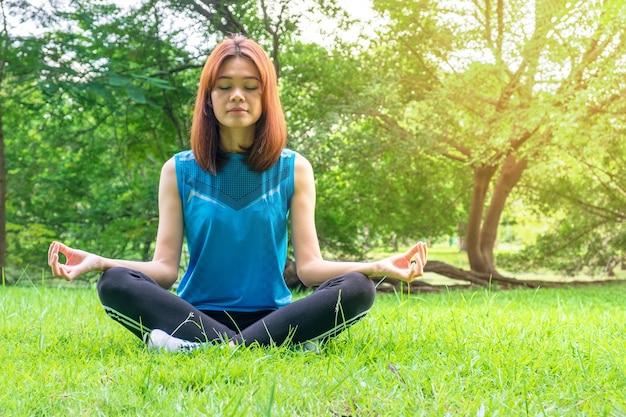 Jovem, mulher asian, olho fechar, e, prática, sentar, ioga, ao ar livre, natureza, fundo