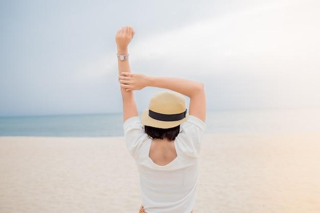 Jovem, mulher asian, relaxante, ligado, praia, vista oceano, férias, ao ar livre, seascape, conceito