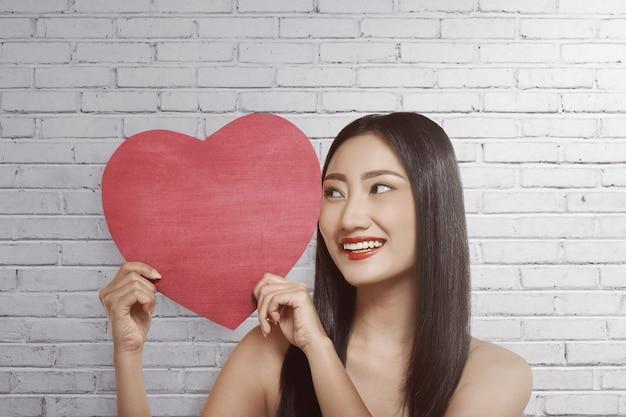 Jovem, mulher asian, segurando, forma coração