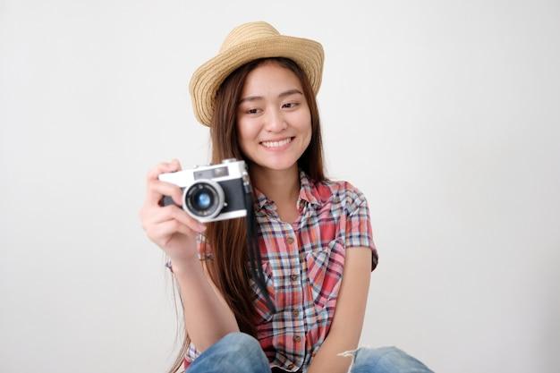Jovem, mulher asian, segurando, vindima, câmera, com, sorrindo, enquanto, preparar, para, viagem