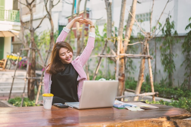 Jovem, mulher asian, sentar-se tabela, frente, laptop
