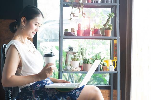 Jovem, mulher asian, usando computador portátil, e, café bebendo, em, café