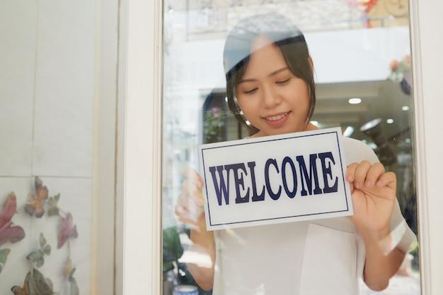 Jovem mulher asiática, abrindo a loja de manhã