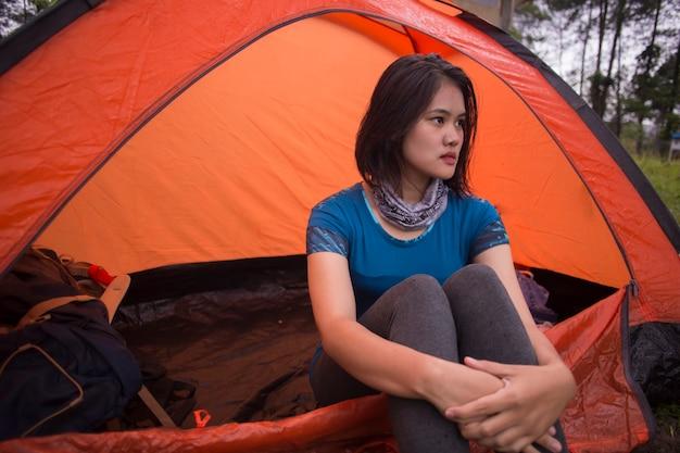 Jovem mulher asiática acampando ou fazendo um piquenique no lago da floresta.